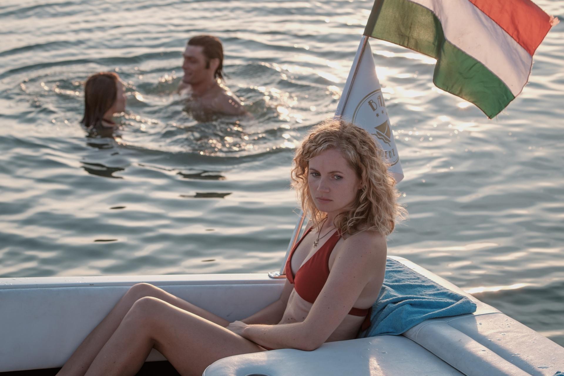 Maja (Sonja Gerhardt, l.) und Tamás (Stipe Erceg, M.) vergnügen sich im Wasser, während Catrin (Cornelia Gröschel, r.) betreten im Boot sitzen bleibt.